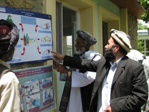 Azimullah, Abudullah Rashid, Mohammad Sharif and Mohammad Nazir discuss messages about birth preparedness and newborn danger signs in Jhpiego-developed posters.
