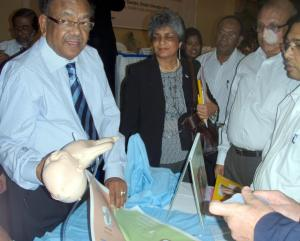 Bangladesh Minister of Health and Family Welfare, Dr. Ruhal Haque, demonstrates newborn resuscitation at Helping Babies Breathe presentation in Bangladesh. MCHIP Director, Koki Agarwal, is on his left.