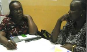 Jhpiego's Rosemary Kamunya reviews a training exercise with a trainer.