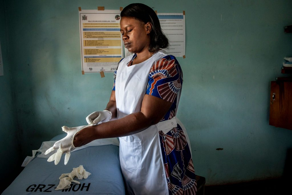 Nurse putting on gloves.