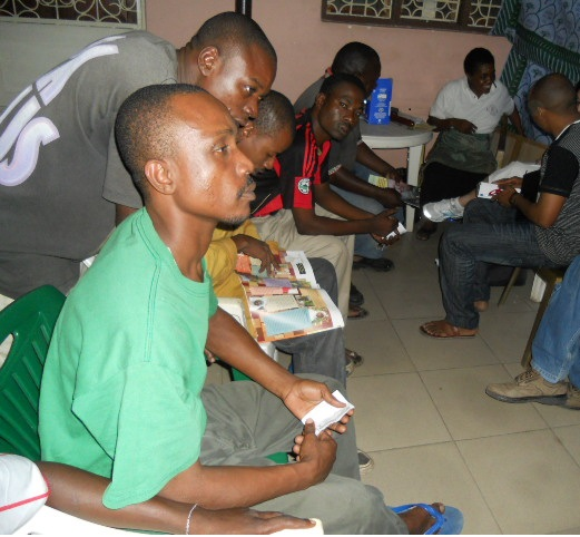 Patrons of the Arizona Bar in Tanga, Tz. wait their turn to discuss HIV prevention and participate in voluntary counseling and testing as part of a special outreach event.