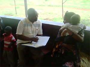 Patrick Mose of APHIA II Eastern counseling a mother at Kina Health Centre on malaria prevention