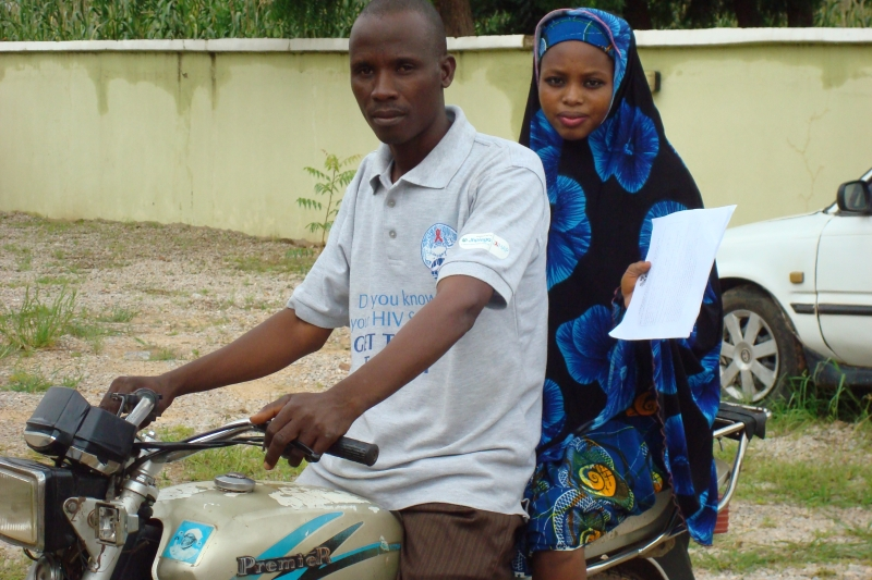 Community volunteer Aminu Mukhtar escorts client Mariya Ibrahim to the Federal Medical Center in Kano, a comprehensive treatment site supported by Institute of Human Virology (IHVN)
