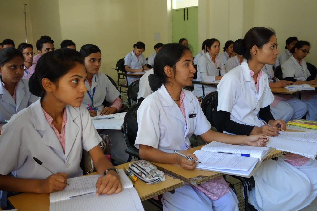 Nursing students at their desks in a classroom.