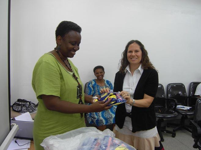 A woman hands a health care worker supplies.