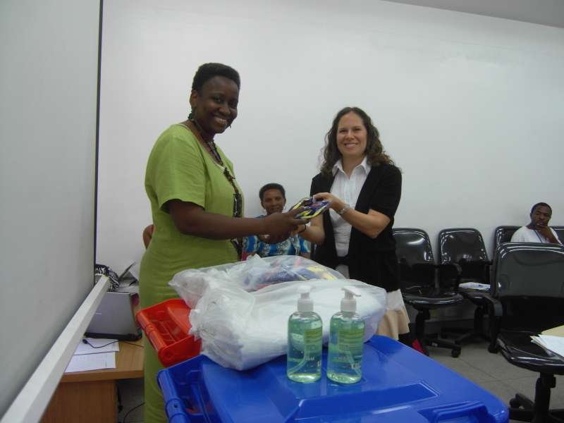 Muhimbili National Hospital Executive Director, Dr Marina Njelekela, receives USAID-donated infection prevention equipment and supplies from Jhpiego's Natalie Hendler.
