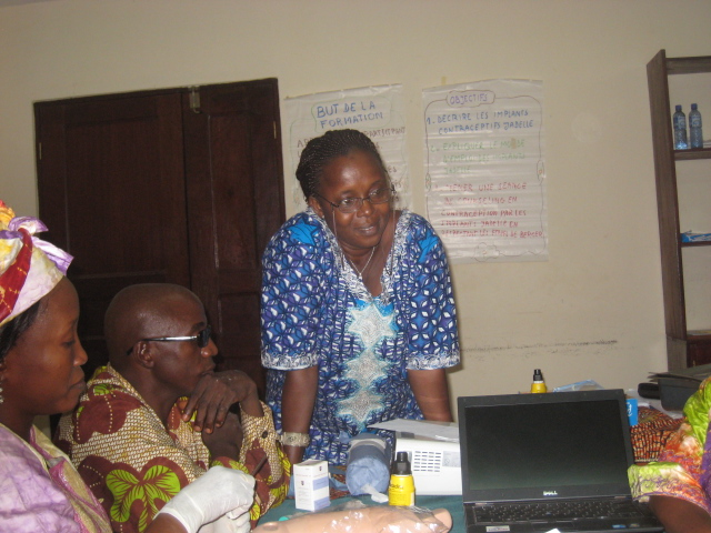 Dr. Sire Camara (standing) has helped lead gains in use of family planning services by women receiving care at the clinic where she works in Conakry, Guinea.