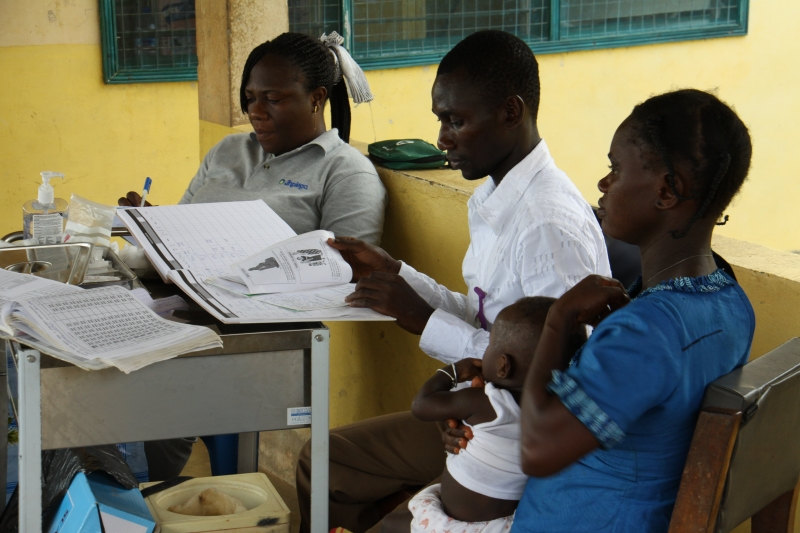 Community health officer Joseph Appiah-Kubi (center) reviews health information with a client at the Akwidaa Community-Based Health Planning and Services (CHPS) center.
