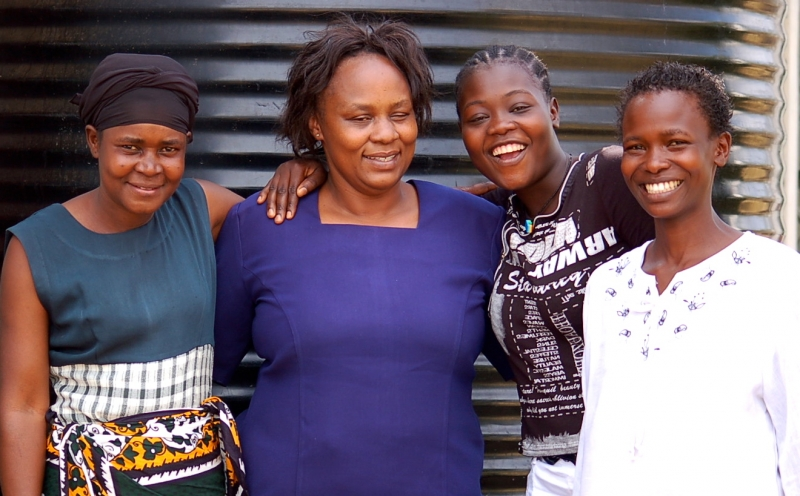 Beatrice Obare (second from left), the frontline health worker in charge at a Tupange-supported clinic in Kisumu,Kenya, poses with members of the Young Mothers Club and satisfied family planning clients, Fausia, Mary and Eunice. (Photo by M.Dotson)