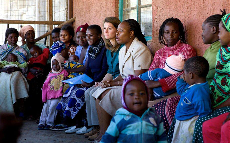 Jhpiego's Jane Otai escorts Melinda Gates as she visits with young Kenyan mothers who are participating in an urban health program in a slum outside Nairobi.