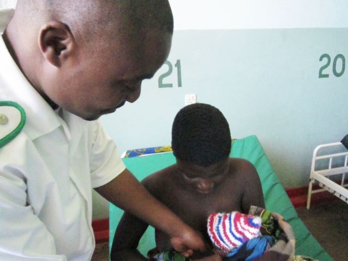 A nurse assisting a new mother to tie her baby to her chest at Balaka District Hospital.