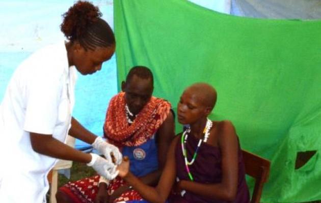 Jhpiego alumna Nurse Frimina Mashele performs an HIV test on Zaina Tukuya at Mafiga Health Center's prenatal care station as her husband, Saitoti Lukuwa, waits for his turn.