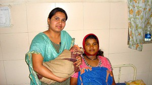 Nurse Archana Kale (left) holds the newborn son of Maya Vikas Jadhav (right). Kale helped resuscitate the baby boy after his birth.