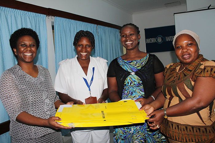 Jhpiego Infection Prevention and Control Senior Program Officer Lemmy Mabuga handing over a donation of 600 safety boxes for collecting and disposing used needles and syringes to Amana Hospital (L-R) Matron Evelyn Rwezaula, Head of Quality Improvement Services Lucy Mbosi, and Hospital Administrative Secretary Tunu Mwanchali.