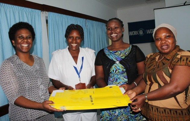 Jhpiego Infection Prevention and Control Senior Program Officer Lemmy Mabuga (L-R) hands over a donation of 600 safety boxes to Amana Hospital Matron Evelyn Rwezaula, Head of Quality Improvement Services Lucy Mbosi, and Hospital Administrative Secretary Tunu Mwanchali.