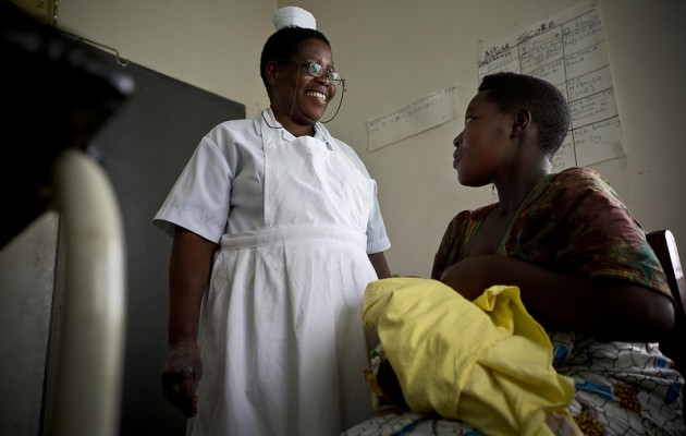 Grace Rutandaro, a midwife who has participated in emergency obstetric care training held by Jhpiego, discusses infant care with a mother as part of a GE Foundation–supported program to strengthen maternal and newborn health services in two districts in Uganda.