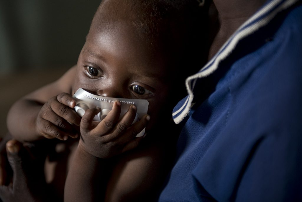 Baby holding malaria medication.