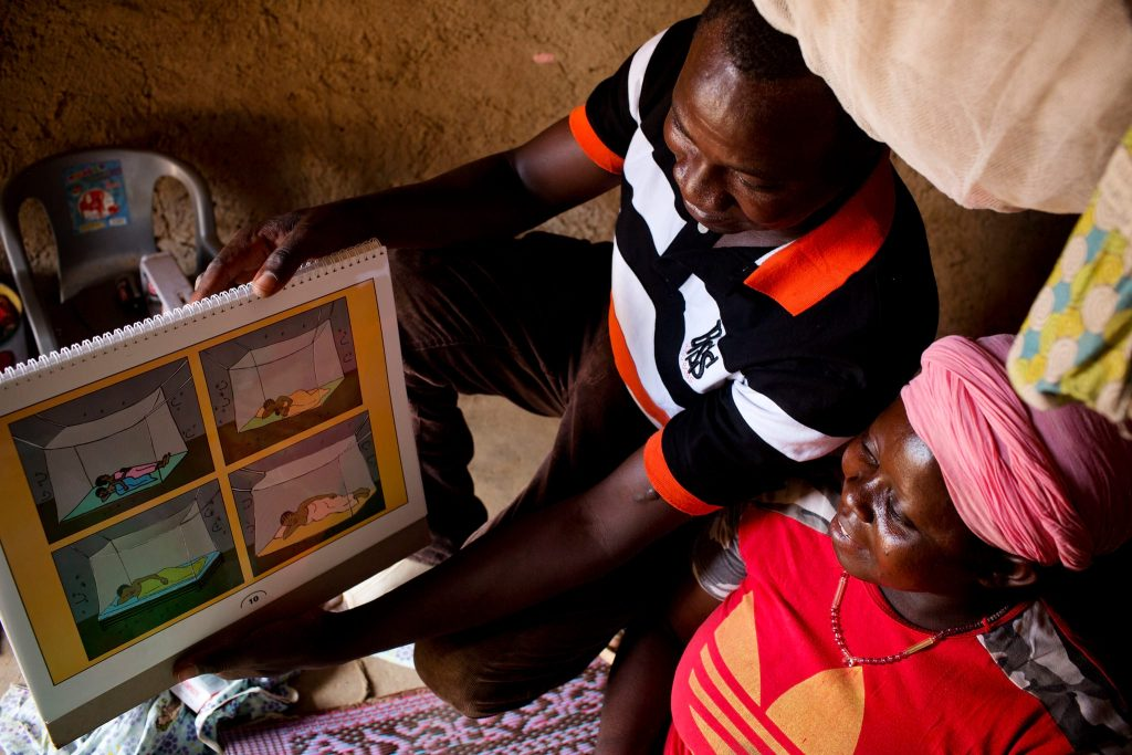 A health worker shows a pregnant women a booklet with illustrations of people sleeping under mosquito netting.