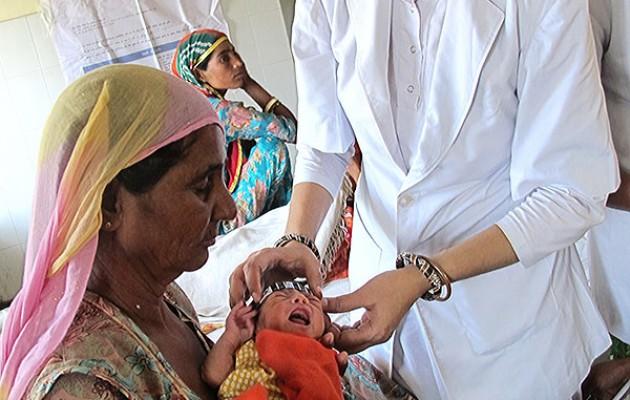 Jaishree checks a newborn's temperature.