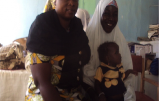 "Joy Osumune, a trained counselor, with Aishat and her daughter. Joy says, ""Following the counseling, today, Aishat is very healthy, her baby is doing well and the family is united."""