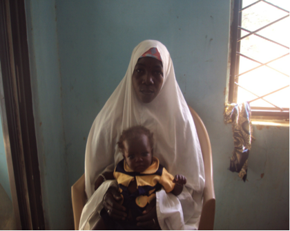 Aishat Yushehu, happily showing off her healthy three-year-old daughter.