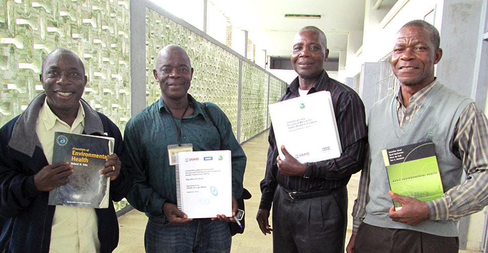 Kerkulah Kollie (second from left) stands with colleagues, displaying their updated training materials.
