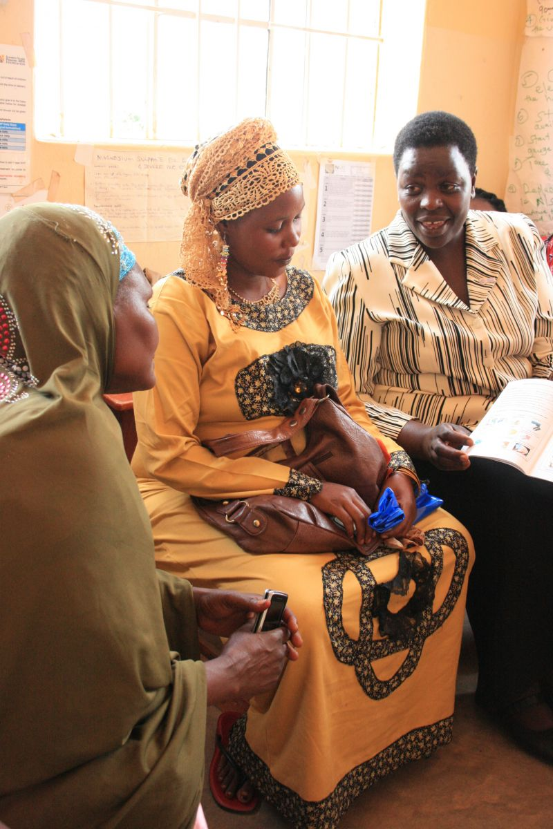Pregnant with her first child, Shadia (center) attends an antenatal care visit at the Kyeirumba Health Center at the insistence of her mother (left), who praises the facility's improved health care services.