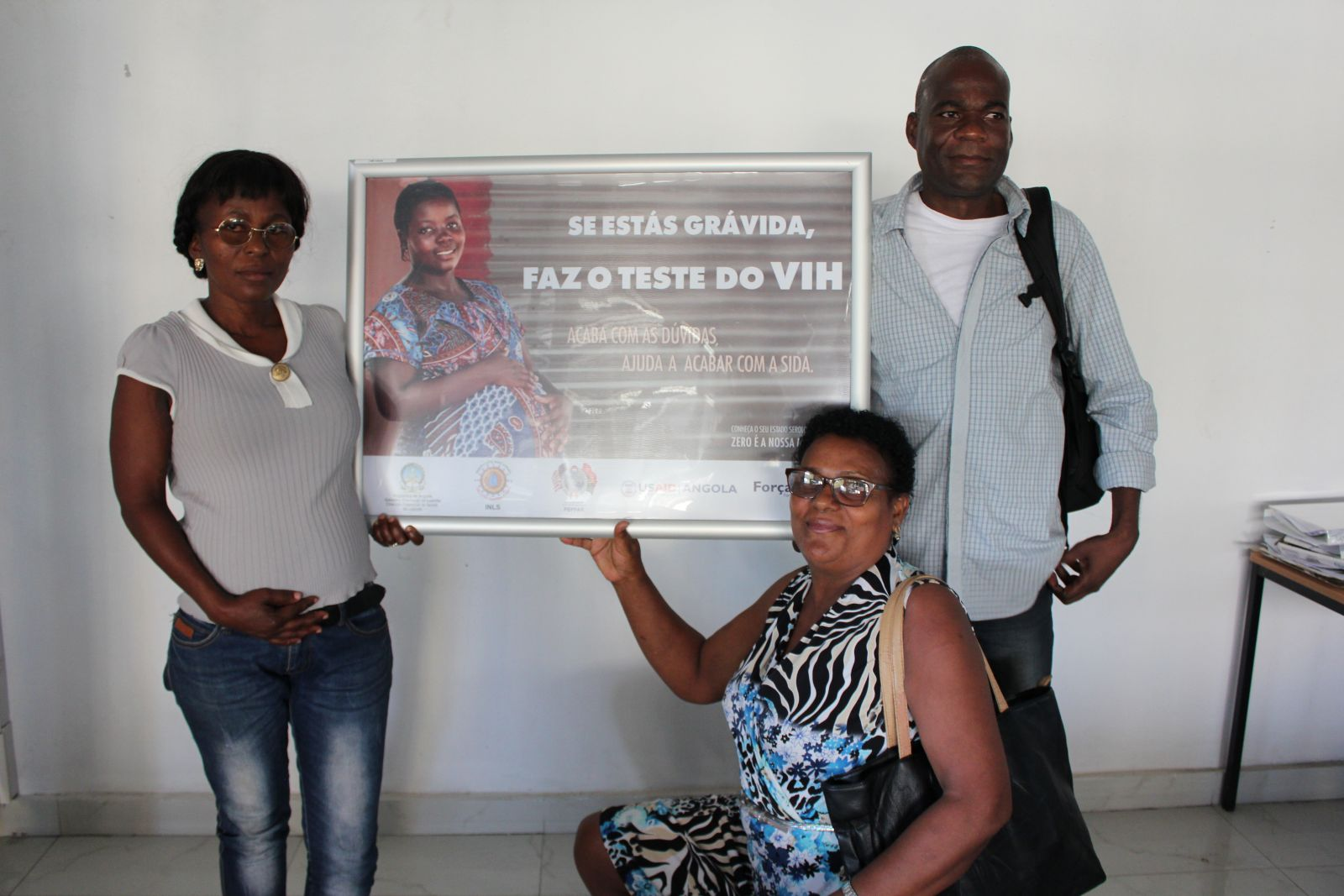 HIV activists Elizabeth Fernandes (kneeling), Francisco Pinto and Suzeth de Morais are helping Angolans with the virus get the treatment and care they need to lead healthier lives.