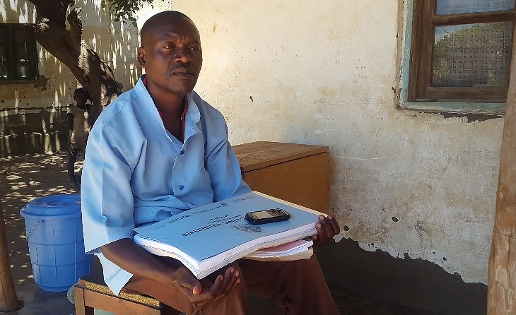 Makono, sitting outside his home in Chimphanga village, is among the Health Surveillance Assistants who help bring malaria prevention and treatment services to women and families in Malawi.