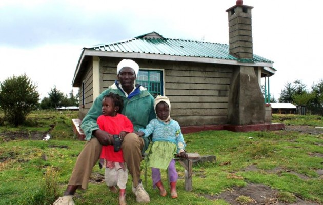 Gerald Mwangi stands in front of his new home that he built with proceeds from his hauling business.