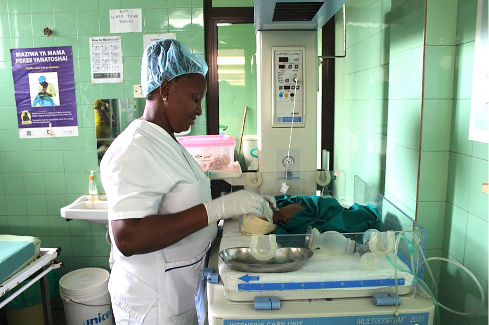 Beatrice Mziray, a nurse-midwife trained by Jhpiego in emergency obstetric and newborn care, uses a simulation model to demonstrate newborn resuscitation with low-cost hand-held equipment.