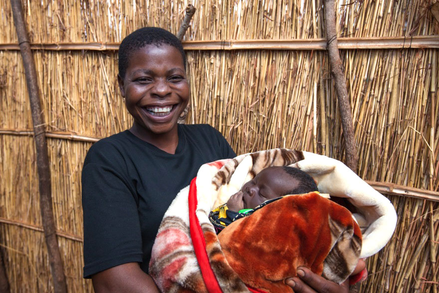 Volunteer Community health worker Sophie holds baby Gloria, whose mother she counseled through pregnancy and childbirth. Sophie visits 30 families each week on foot; she is one of the volunteers who received a pair of shoes donated by TOMS as part of an innovative partnership with Jhpiego.(Photo: Jhpiego/Guido Dingemans)