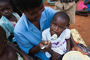 A mother feeds her daughter nutritious porridge made during a cooking demonstration supported by the SSDI project in Thaulo village.