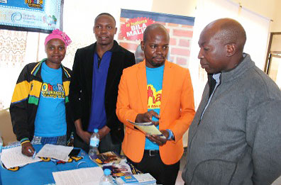 MCHIP VMMC Peer Promoter Ladislaus Ngeresa speaks with a delegate who stopped at their booth.