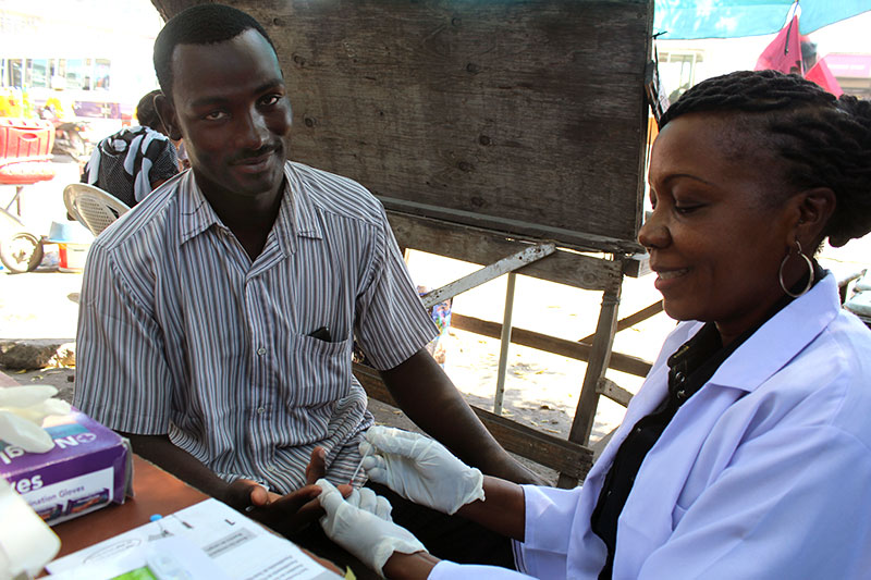 A Sauti Nurse Counselor, Lilian Kayuni drawing blood for HIV testing from Emmanuel George Mwakisu (30), when she visited a bodaboda (motorbike) hangout at Msasani, Macho Street. Sauti program is reaching the mobile men like Emmanuel who is a bodaboda rider to strengthen positive behaviors and social norms at the individual and community levels.