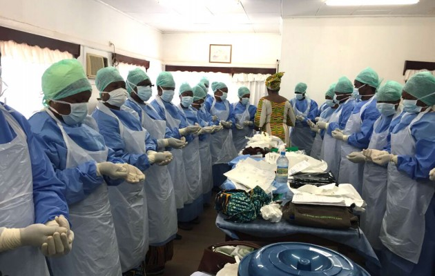 Health care providers participating in a Jhpiego-led infection prevention and control training suit up in protective gear.