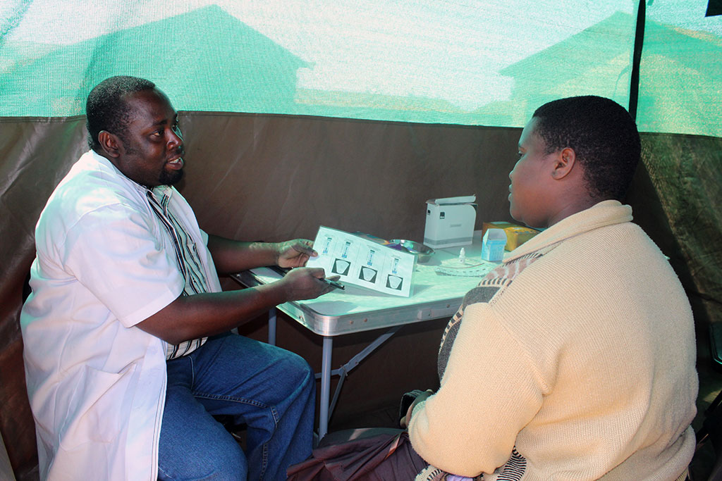 "Tumpe Chaula (right) visits the Sauti project's community-based, mobile HIV testing and counseling ""plus"" service in Njombe Town. Photo by Zacharia Mlacha/Jhpiego"
