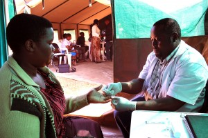 Community health promoter Mohamed Bawzi (right) administers an HIV test for Tumpe Chaula.