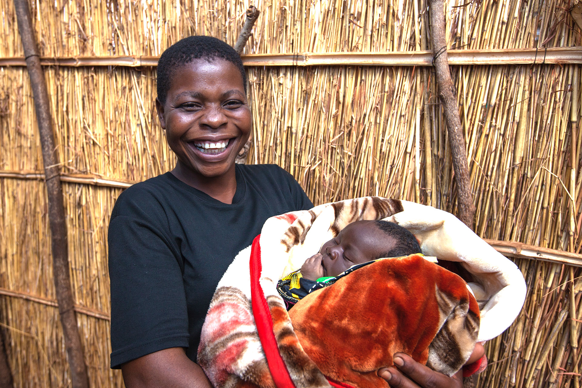Volunteer community health worker Sophie Makoza's smile says it all as she holds baby Gloria