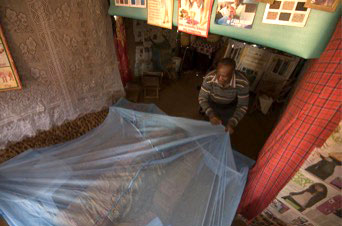 A CHV demonstrates a method to hang a mosquito net over a bed by supporting it with chairs.