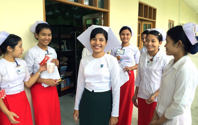 Midwifery instructor Tin Ma Ma Nyein with her students during a break from their studies.