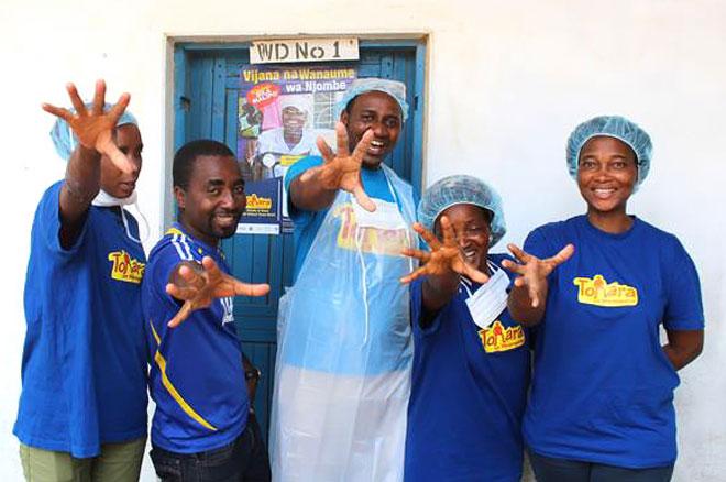 Njombe, Tanzania—VMMC providers at Itulahumba Dispensary give a high five to celebrate the 500,000 VMMC milestone.