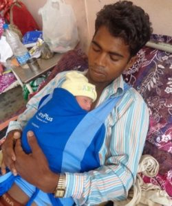 A father practices kangaroo care with a new wrap designed by Laerdal to encourage this practice.