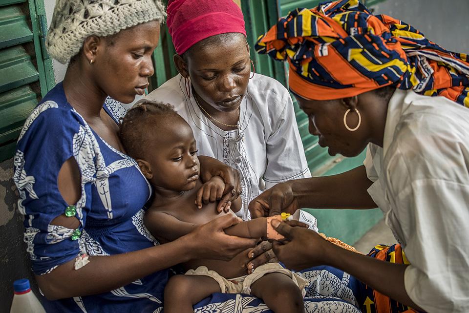 Nurse treats a child with severe malaria