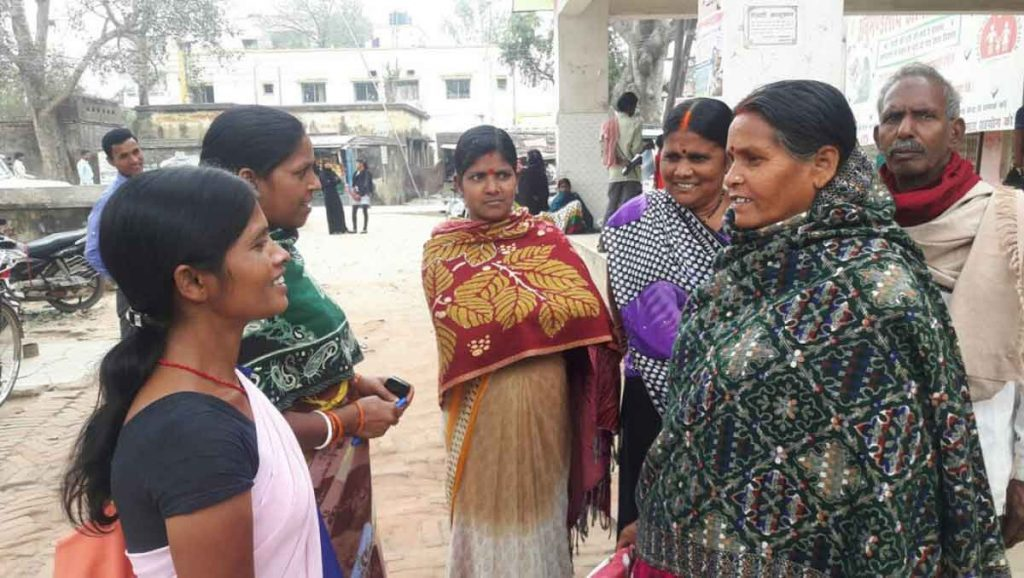 An ASHA worker talking to clients in their community