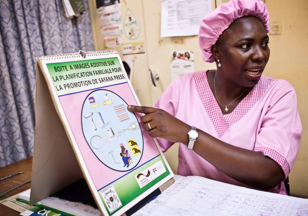 A midwife pointing to a chart showing different types of family planning methods