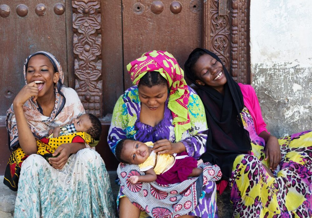 Three young women, two with infants, sit outside a building smiling.