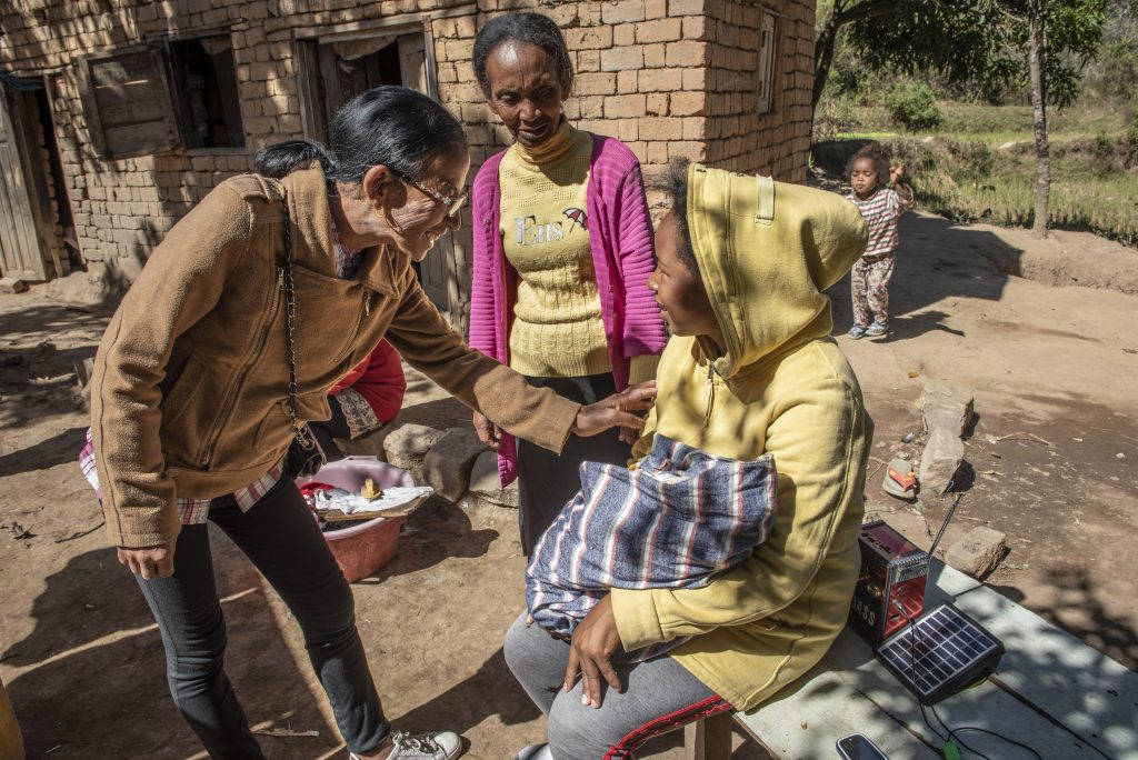 Two community health workers visiting new young mother in Madagascar.
