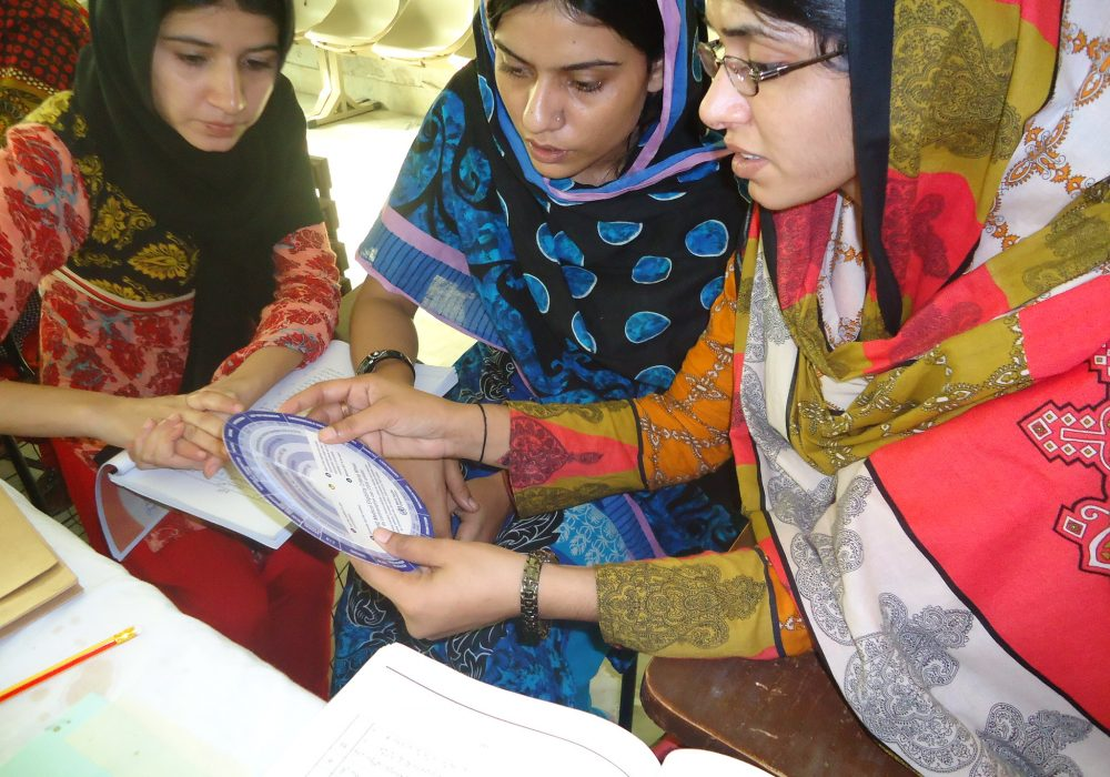 Three female health providers in Pakistan receiving training.