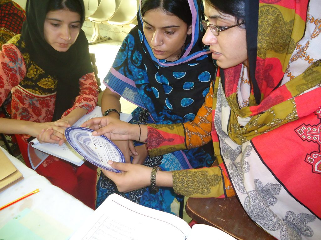 Three female health providers in Pakistan receiving training.